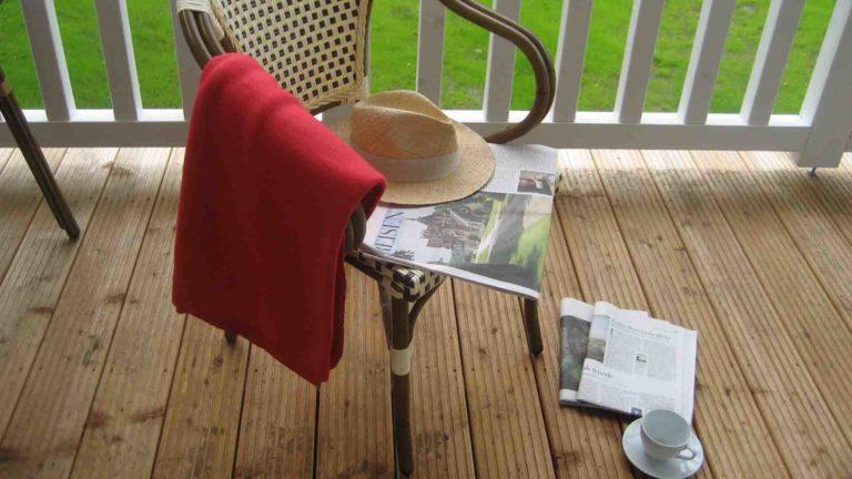 Balkon mit Sessel, Zeitung, Strohhut und Kaffeetasse