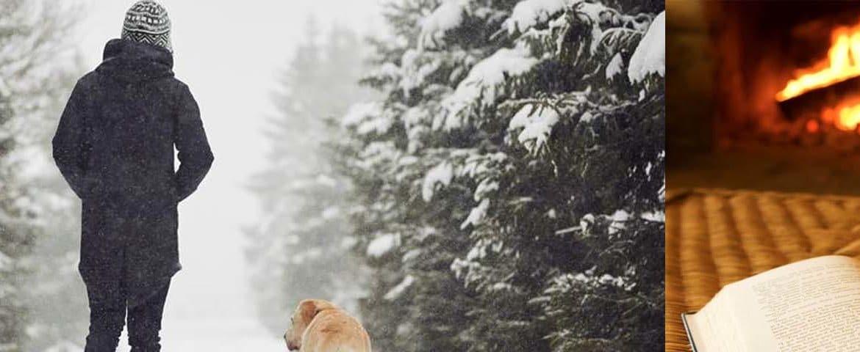 Frau mit Hund im verschneiten Wald