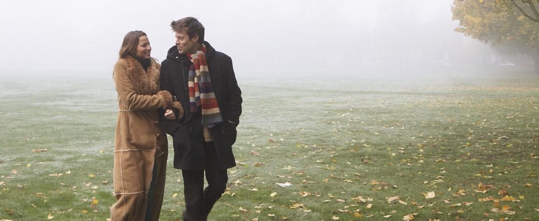 Entspannte Spaziergänger in nebeliger Herbstlandschaft